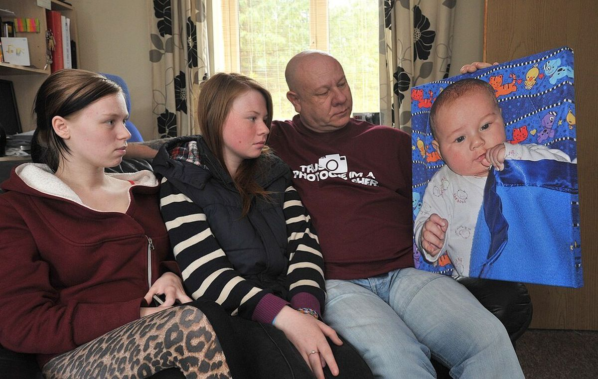 Abbie Perkins, Sophie Perkins, Glen Perkins with a picture of Olivia Perkins at four months old just before she died