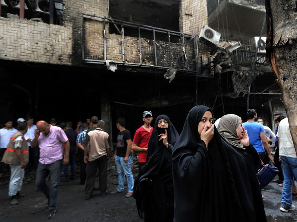 Iraqi women wait to hear about family members who went missing after a bomb hit Karradah, a busy shopping district in the centre of Baghdad, Iraq (Hadi Mizban/AP)
