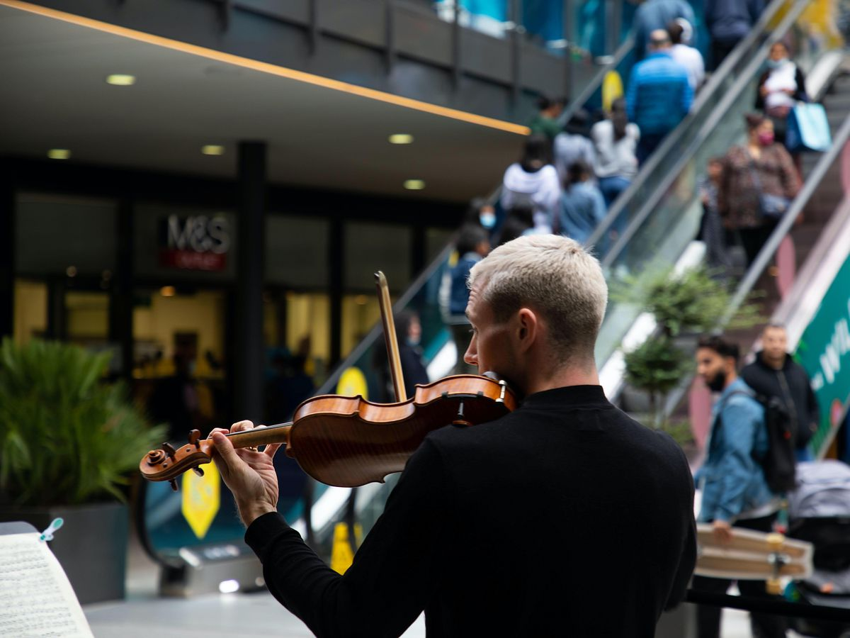 Members of the public watch a surprise appearance by the Royal Philharmonic Orchestra in Wembley
