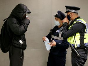 Police officers speak to a member of the public