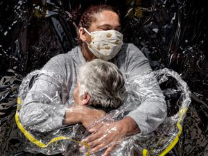 The winner of World Press Photo of the Year award, and the first prize in the General News Singles category, showing Rosa Luzia Lunardi embraced by nurse Adriana Silva da Costa Souza, at Viva Bem care home, Sao Paulo, Brazil (Mads Nissen, Politiken, Panos Pictures, World Press Photo via AP)