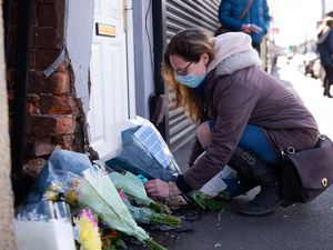 A woman lays flowers at the scene on High Street, Brownhills, near Walsall in the West Midlands, where a two-week-old baby boy in a pram was hit by a BMW car at around 4pm on Easter Sunday. West Midlands Police said the baby was rushed to hospital but nothing could be done to save him. Picture date: Monday April 5, 2021. PA Photo. The driver of the BMW left the scene but a 34-year-old man was arrested in Bloxwich shortly afterwards and taken into custody where he will be questioned on suspicion of causing death by dangerous driving. See PA story POLICE Pram . Photo credit should read: Jacob King/PA Wire.