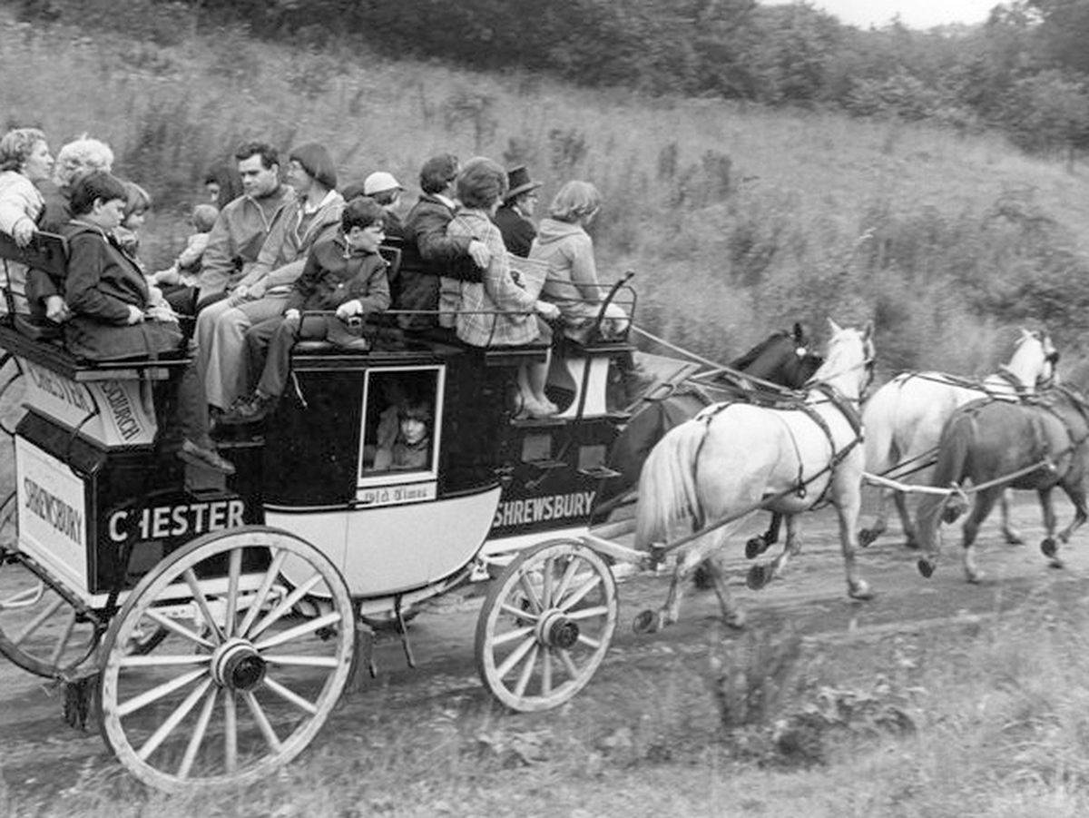 """The Old Times stagecoach in action carrying visitors at Blists Hill, driven by Phil Holder, with young groom Karen Stevenson sitting on the """"wrong"""" side to operate the brake."""