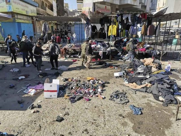 People and security forces gather at the site of a deadly bomb attack in a market selling used clothes in Iraq