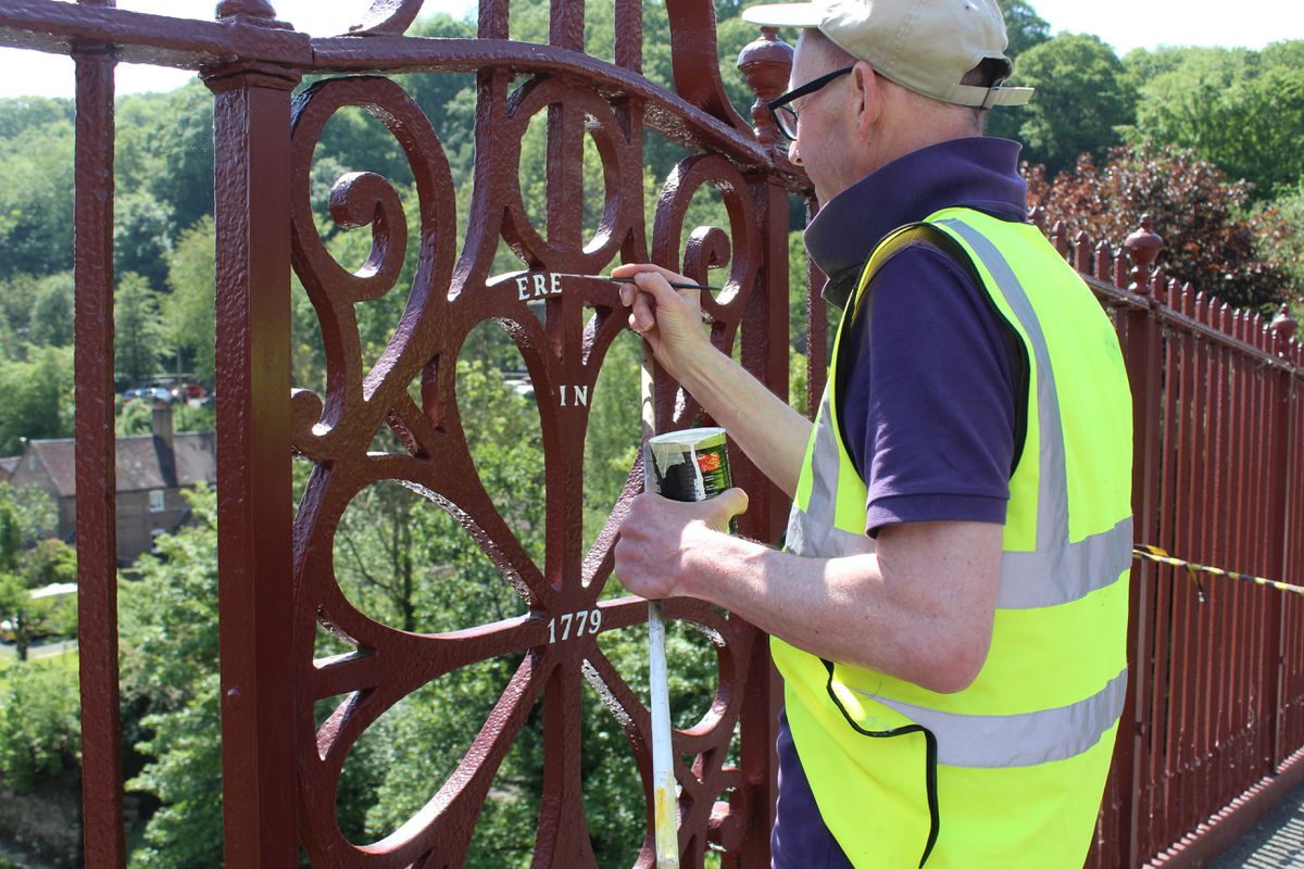 Sign-writer Phil Barber picks out the lettering on the bridge