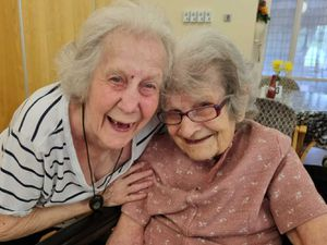 Gladys Cloke receives a birthday hug from fellow resident and friend Joan Sivill on her 110th birthday