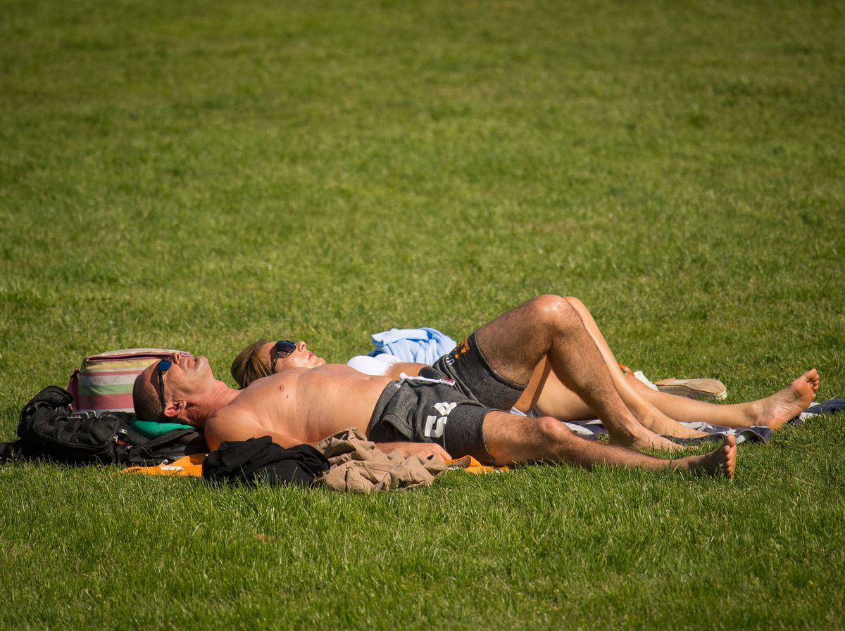 People enjoy the warm and sunny weather in Greenwich Park, south London, on what is set to be the hottest May Bank Holiday Monday since records began. PRESS ASSOCIATION Photo. Picture date: Monday May 7, 2018. See PA story WEATHER Hot. Photo credit should read: Dominic Lipinski/PA Wire ..