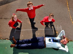 Headteacher Tom Plim, gets measured in feet, literally, by pupils: Bea Steadman, Finn Walford and Zac Mantle, all aged six