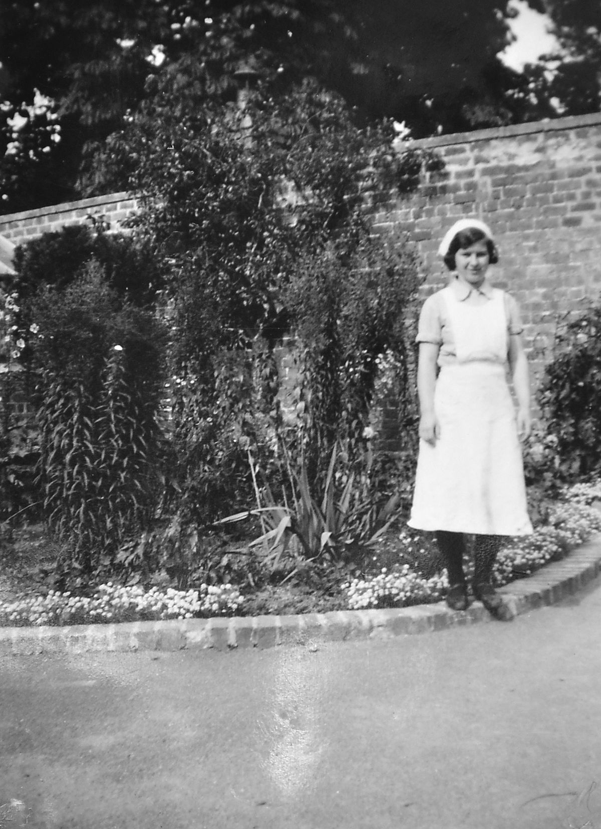 In her uniform going into service as a 14-year-old cleaner at The Grange, West Felton