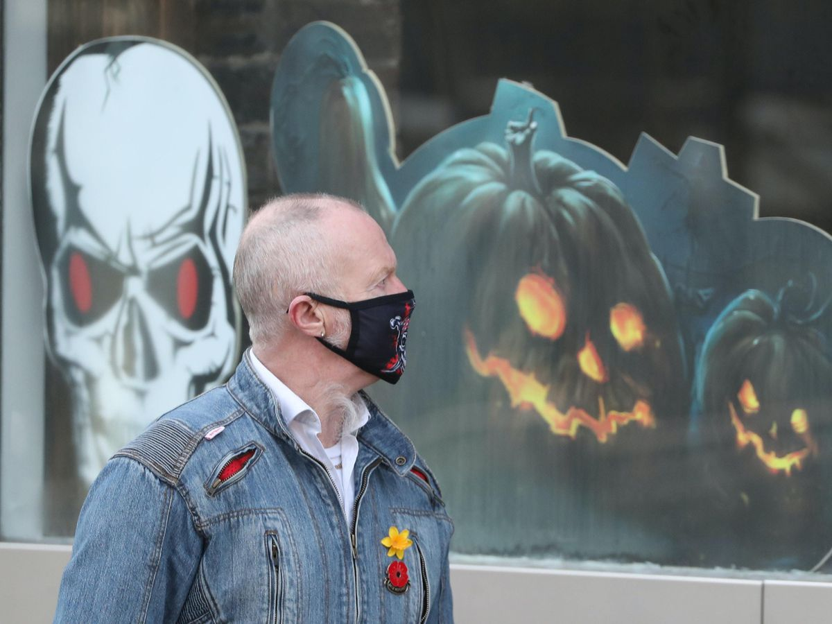 A man walks past a shop with Halloween decorations in Hamilton