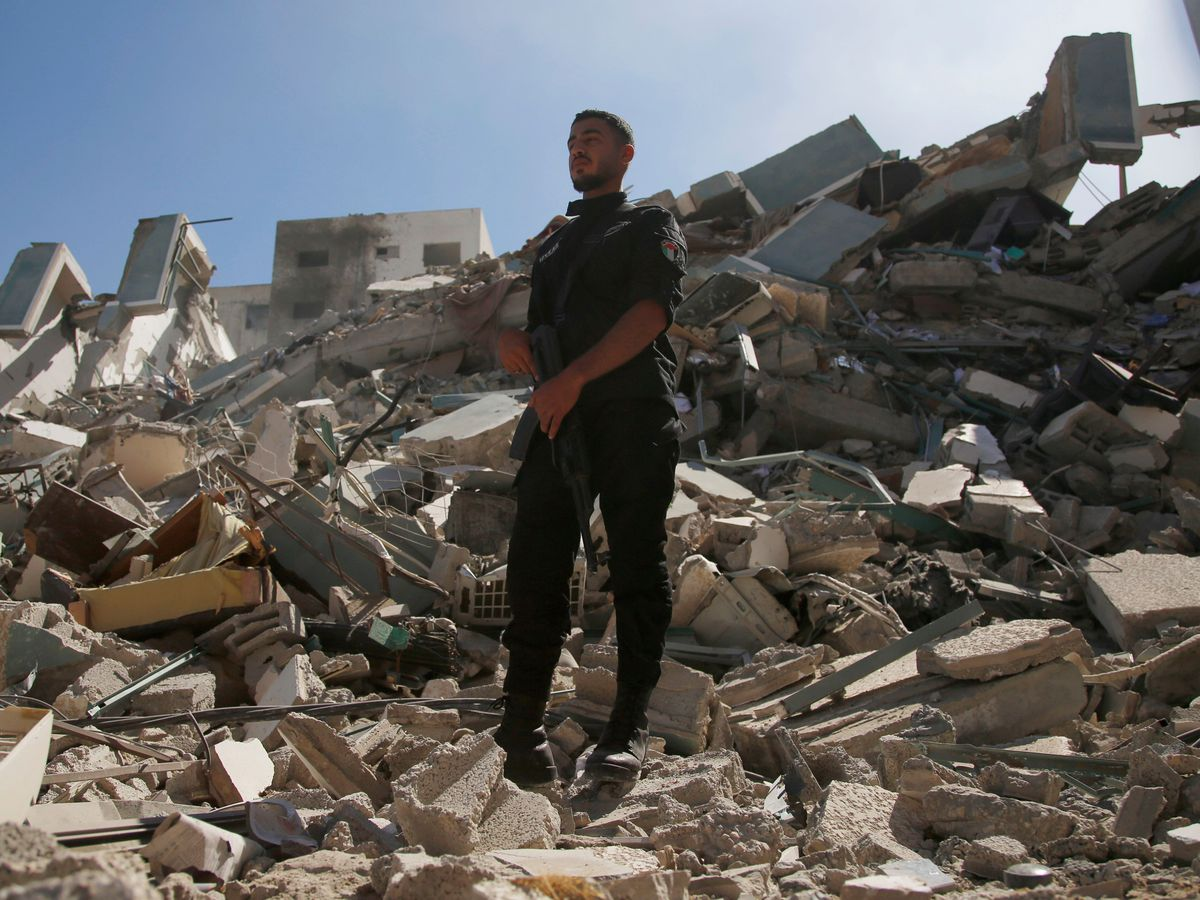 A policeman stands on rubble from a building housing AP office and other media in Gaza City that was destroyed after Israeli warplanes demolished it