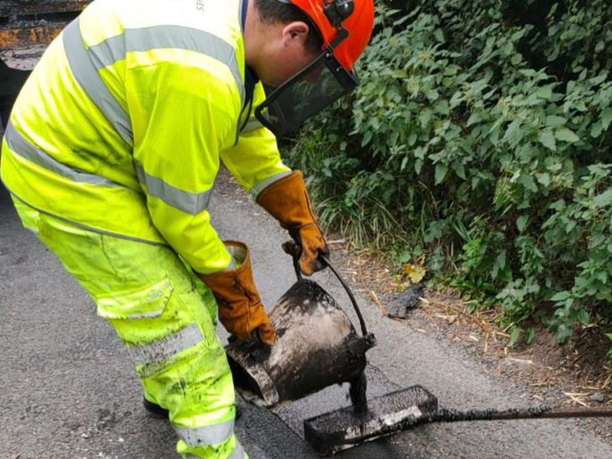 A worker repairing a pothole through Texpatching