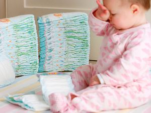 A baby surrounded by disposable nappies