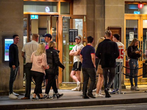 Young people queue to get into a pub in Cardiff city centre at night (Ben Birchall/PA)