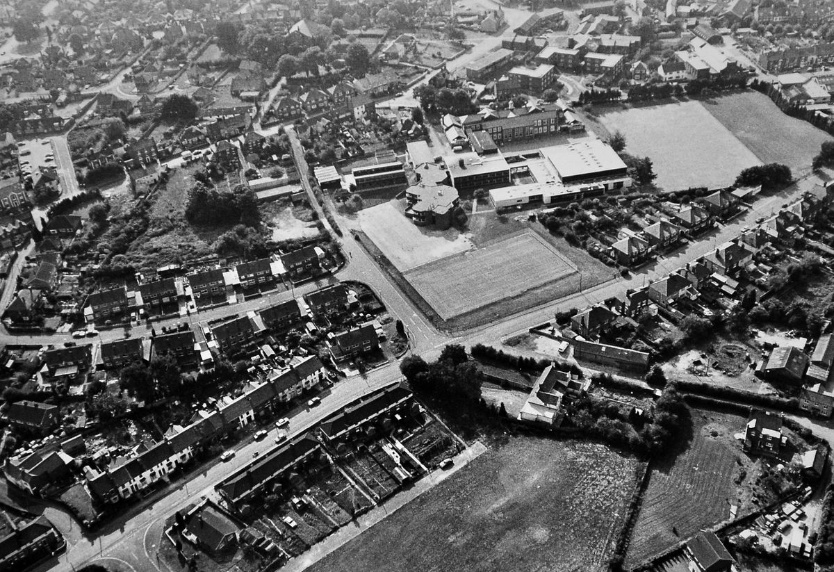 The campus of New College, Wellington, dominates this aerial picture from September 1983. It shows how the former girls' high school building had been enlarged to cater for sixth form students from throughout Telford. In the foreground is Regent Street.