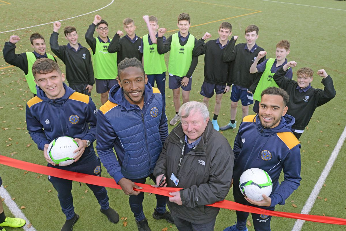 Players, from left, Ryan Giles, Omar Beckles and Louis Thompson, are joined by chair of governors Geoff Corfield and pupils
