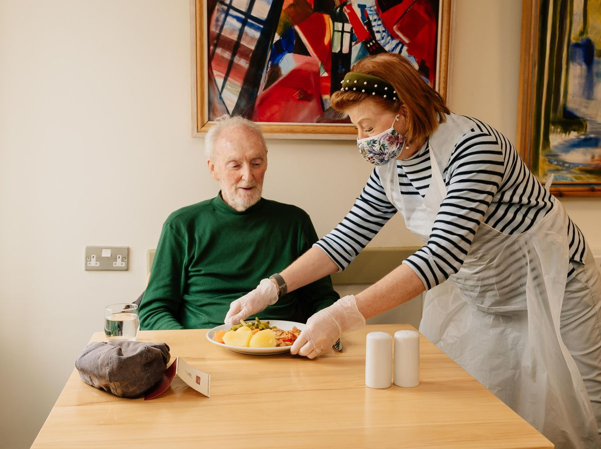 Volunteer Madeline Egan serving food