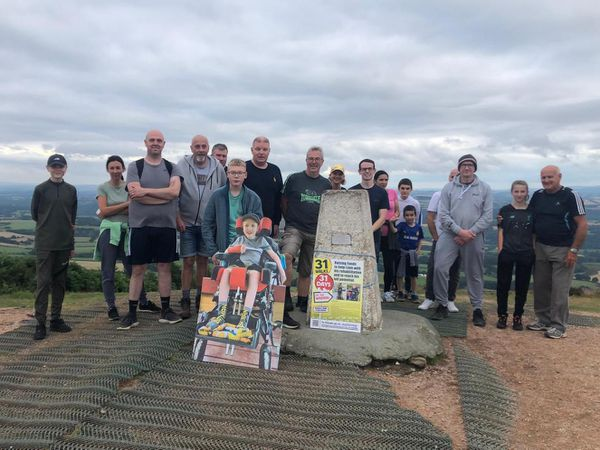 John, joined by Liam's father Andy, his brother Callum, and friends and family, at the top of the Wrekin for the final leg of the challenge.