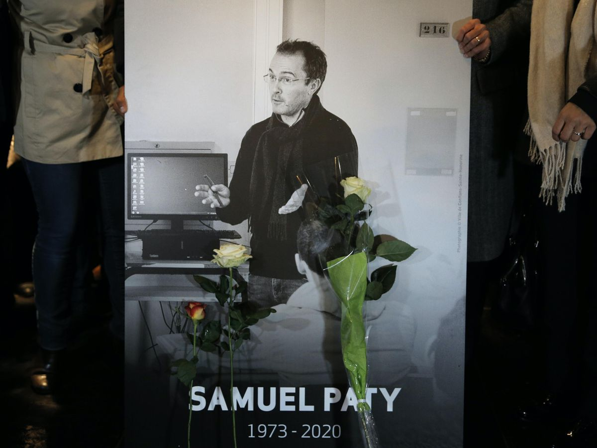 People hold a photo of the history teacher Samuel Paty