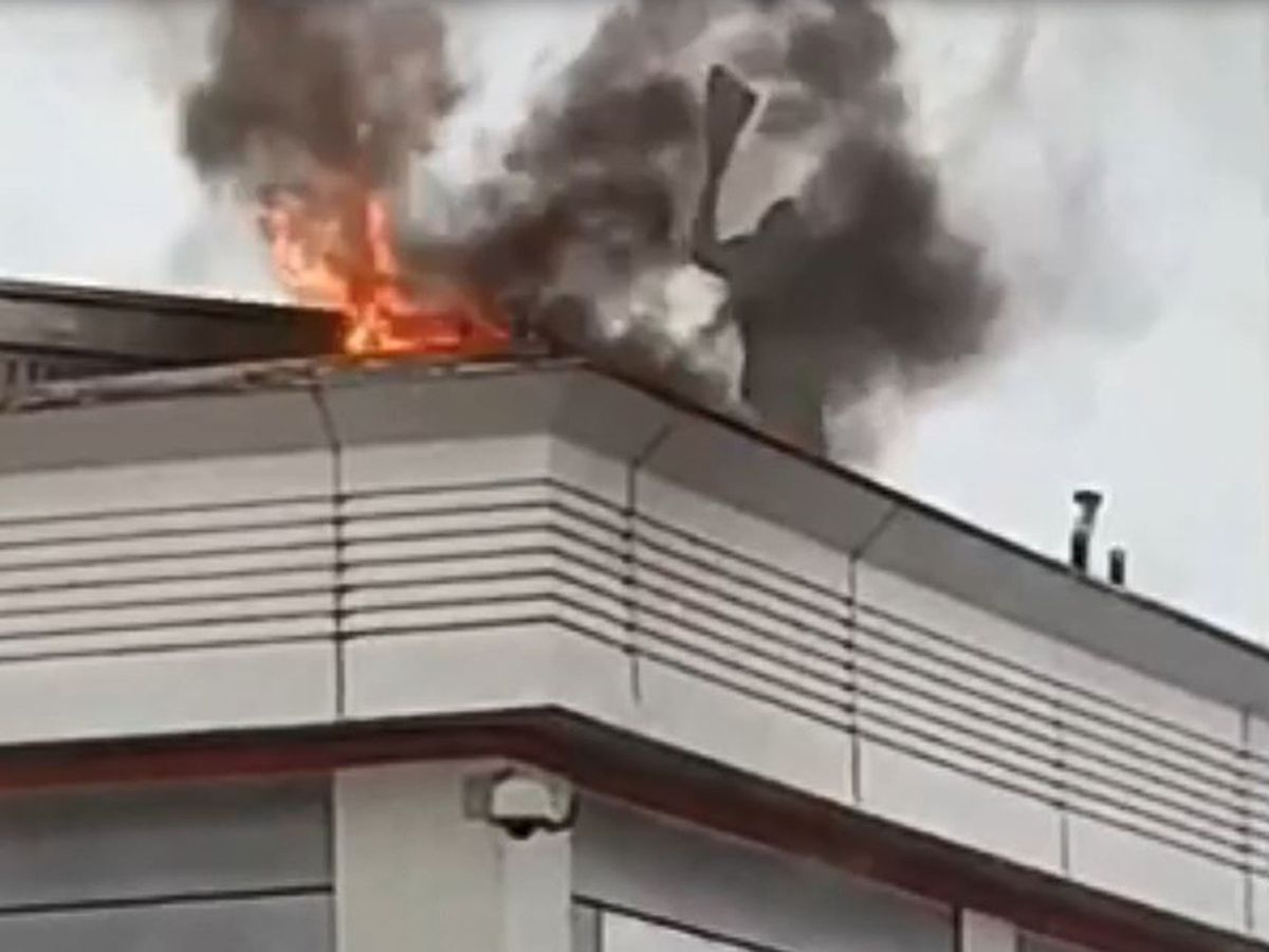 Video still of worker on roof trying to put the fire out