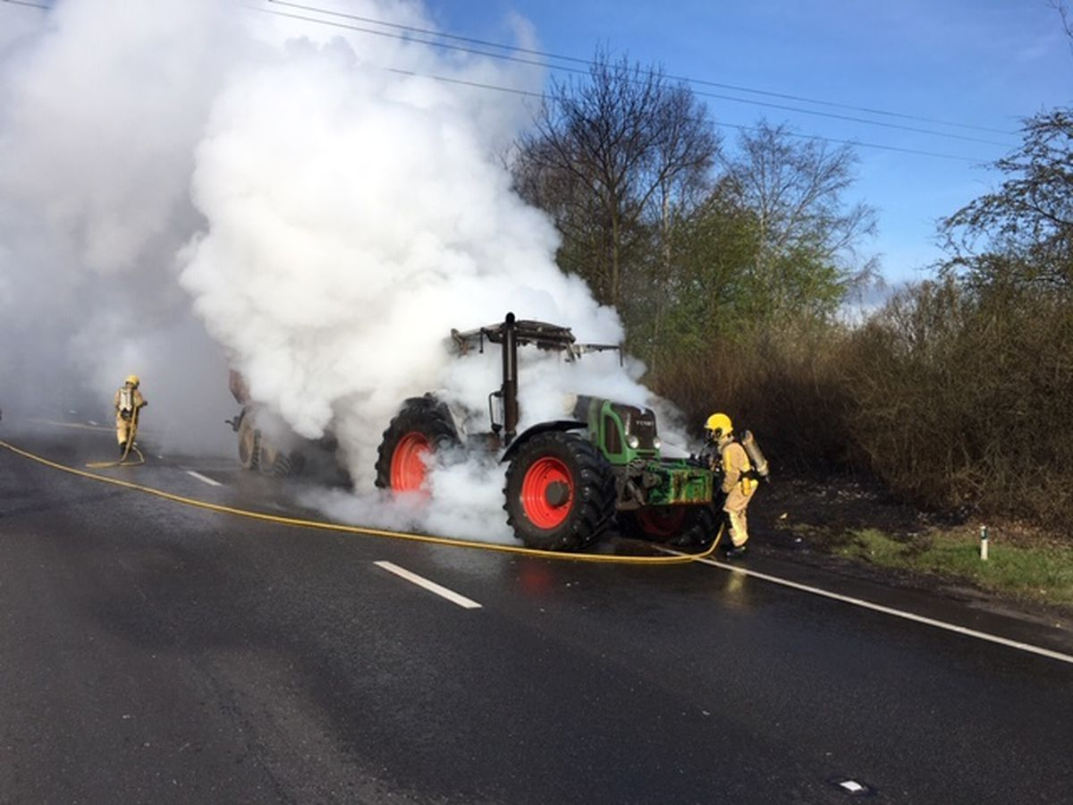 Firefighters tackle the tractor blaze on the A5. Picture: Chris White, Shropshire Fire and Rescue