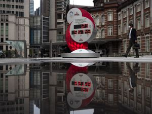 A countdown clock for the Tokyo 2020 Olympics is reflected in a puddle of water outside Tokyo railway station