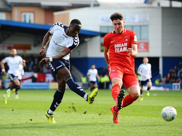 Dan Udoh of AFC Telford shoots under pressure from Dan Happe of Orient during the FA Trophy Semi Final fixture between AFC Telford United and Leyton Orient at the New Bucks Head