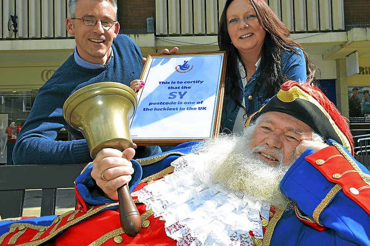 Town crier Martin Wood celebrates with Lotto winners James and Sue Schofield that SY is one of the luckiest postcodes