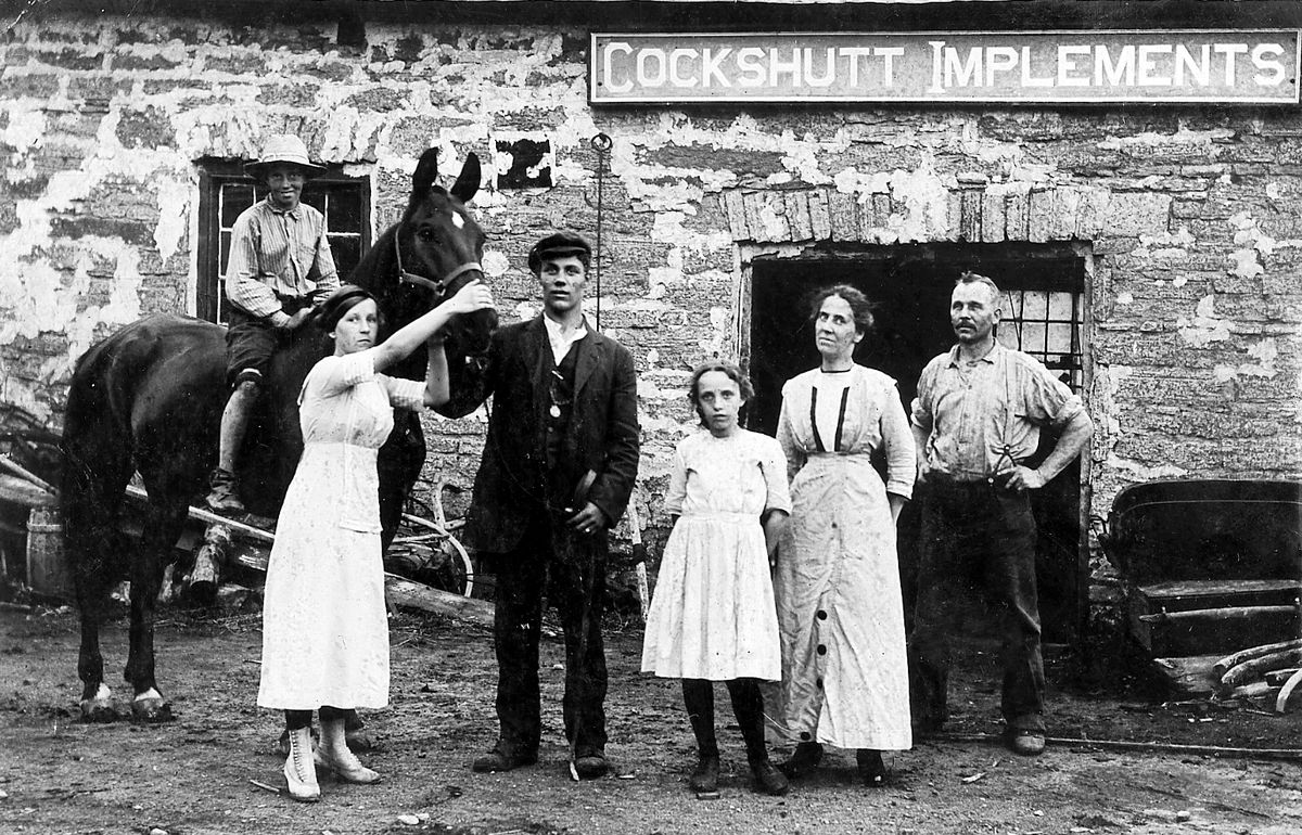 We know this group is posing outside Cockshutt Implements – but where?