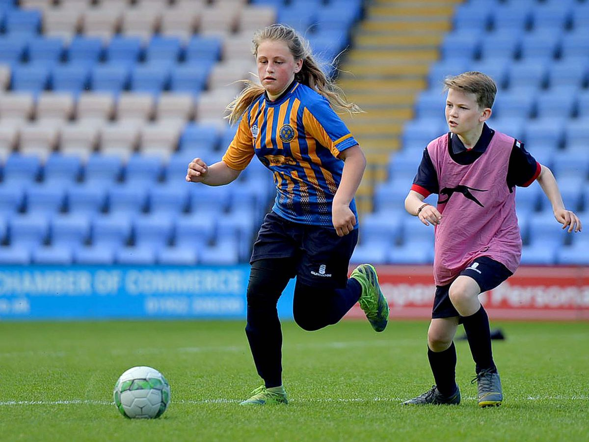 Pupils Rubie Francis and Joshua Moran battle it out on the Shrewsbury Town pitch