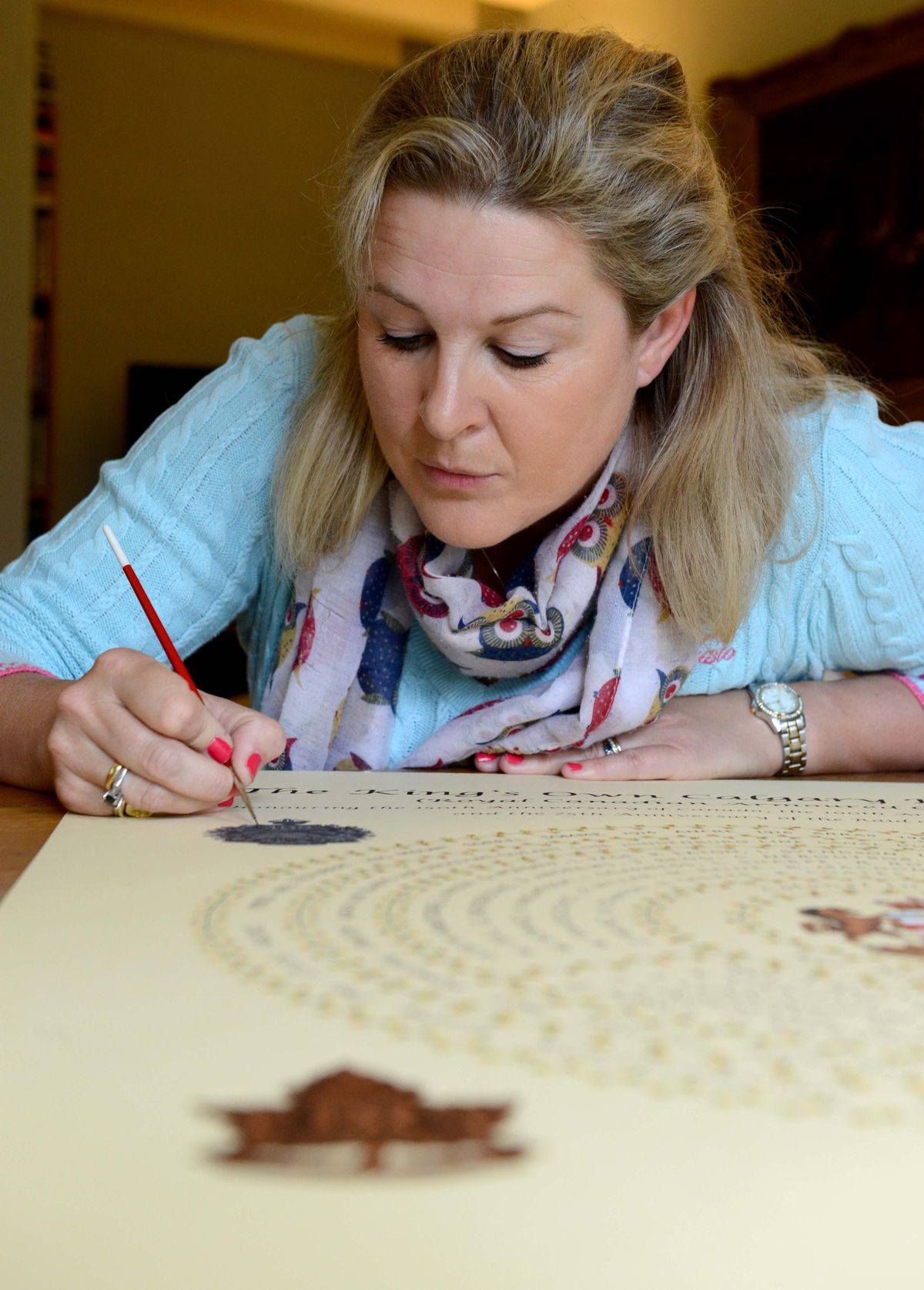 Artist Clare Villar putting the finishing touches to a piece commissioned by The King's Own Calagary Regiment to commemorate 100 years since Vimy Ridge