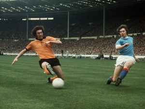 Manchester City's Willie Donachie (r) crosses the ball past Wolverhampton Wanderers' Geoff Palmer (l).