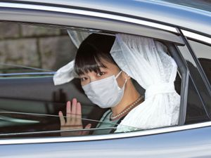 Japan's Princess Mako waves from a car as she leaves her home in Akasaka Estate in Tokyo