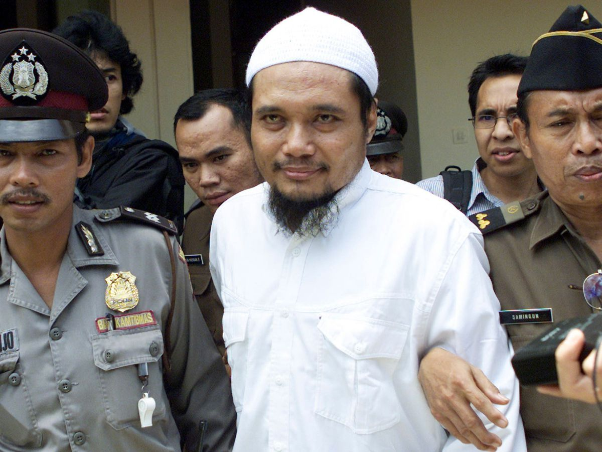 Militant cleric Abu Rusdan, centre, is escorted by security officers after his trial hearing at a district court in Jakarta, Indonesia (Tata Syufiana/AP)