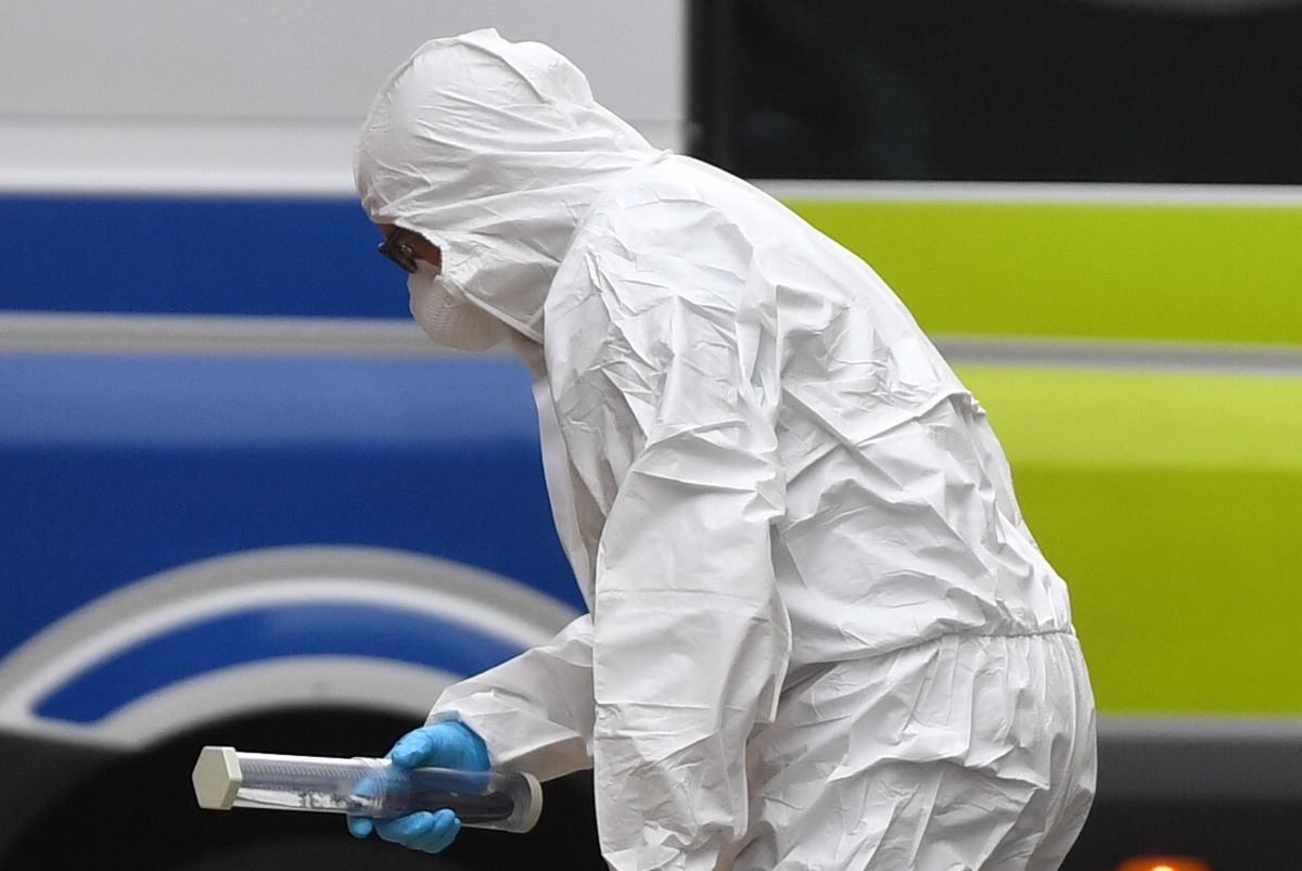 A forensics officer holding a sealed container with a black handled knife inside in Edmund Street