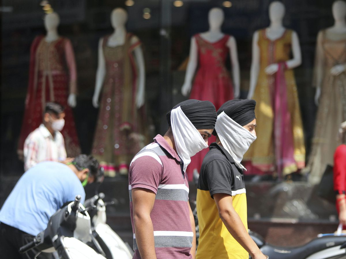 Indians wearing face masks as a precaution walk in a market area in Jammu