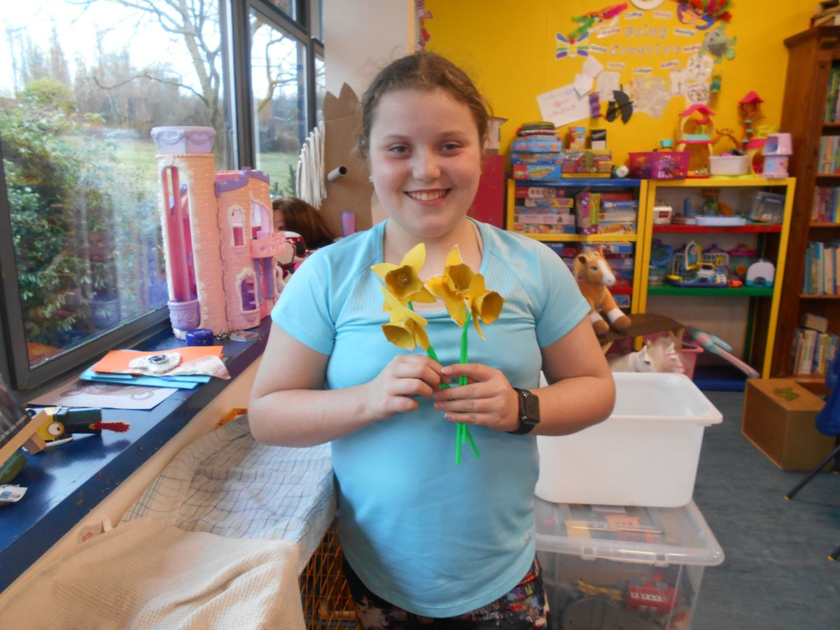 Kara Gledhill proudly showing off a posy of paper daffodils