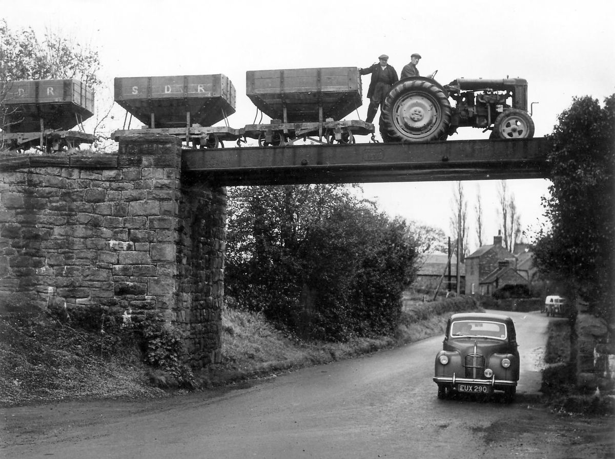 """A train of empty wagons for Callow Hill quarry hauled by the Fordson tractor at Pontesbury, about 1950. Driving is George Philpott Edwards with John Arthur Rowson (""""Jackie Belter"""") standing."""