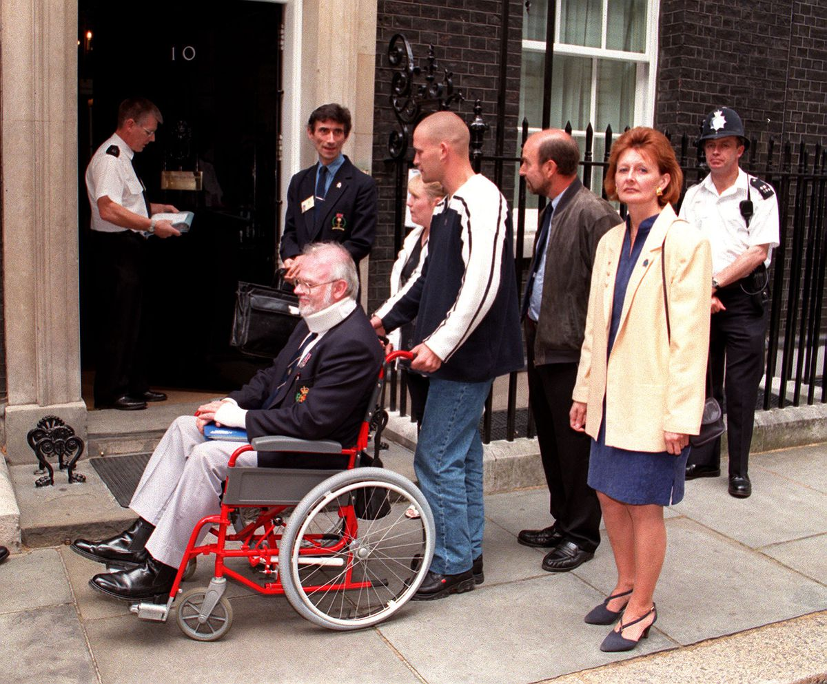 Chairman of the National Gulf Veterans and Families Association Tony Flint and Gulf veteran Brian Tooze, in wheelchair, taking a petition to Downing Street in 1998