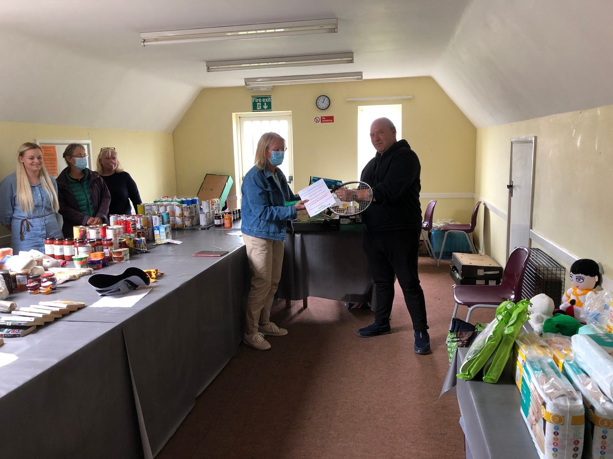 Anne-Marie Jackson presents a prize of six free tennis lessons and three months membership from Bishop's Castle Tennis Club to lucky winner Chris