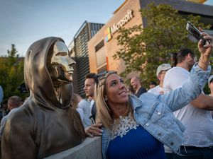 A woman takes a selfie with a newly unveiled statue of the mysterious developer of the Bitcoin digital currency in Budapest, Hungary