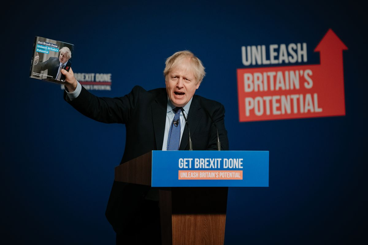Mr Johnson with a copy of the Tory manifesto on stage