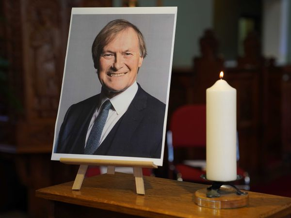 A candle and a photo of Sir David Amess