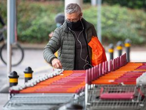 A shopper wearing a face mask outside a Sainsbury's store