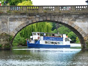 Enjoying a journey down the river in Shrewsbury in the warm weather. The Sabrina boat framed by the bridge in Shrewsbury