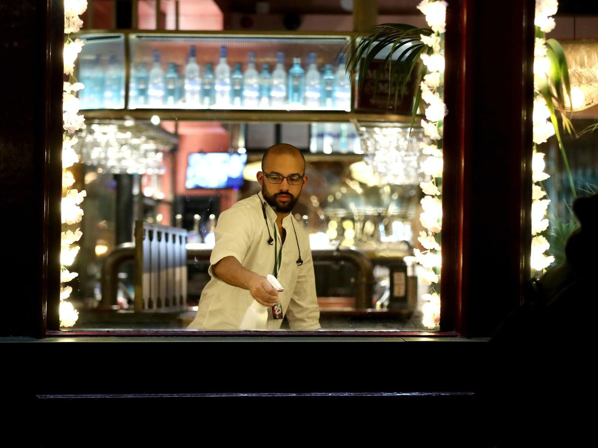 A pub worker cleans the bar