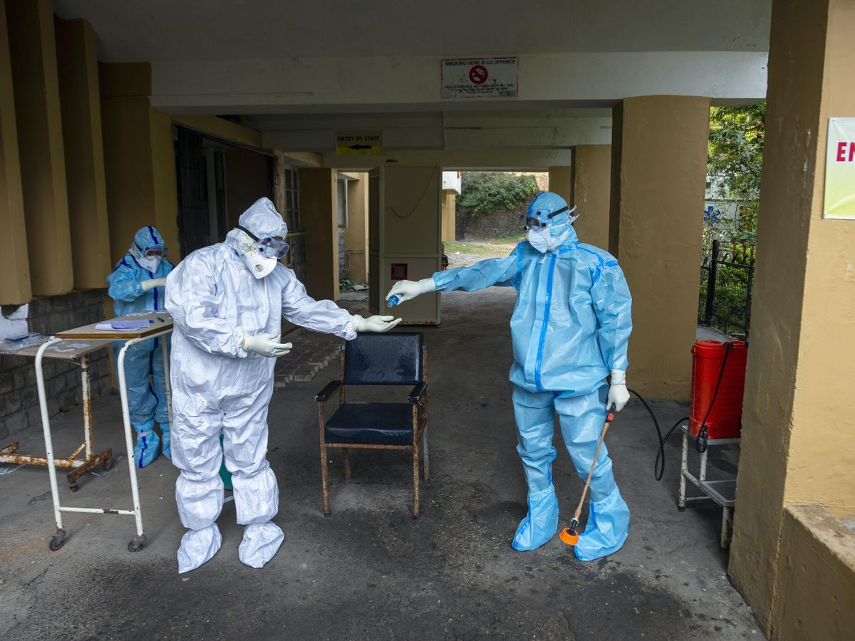 A health officer in protective suit gives hand sanitiser to another at a Covid-19 testing centre in Dharmsala, India (Ashwini Batia/AP)