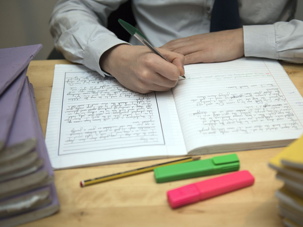 A primary school teacher marking a pupil's English homework (PA)