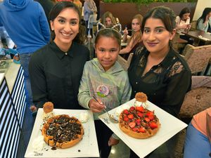 Staff members Shafaq Zahid, left, and Nafeesa Bi with Amberlea Brown who was celebrating her 10th birthday in the new shop