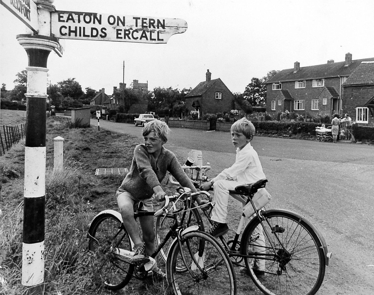 """Sign of past times. The date is August 8, 1967, and the original caption to this photo in our archives was: """"Two boys with time on their hands, Dean Woolley and Malcolm Walker, both from Great Bolas, plan their day under the sign post at Great Bolas."""""""